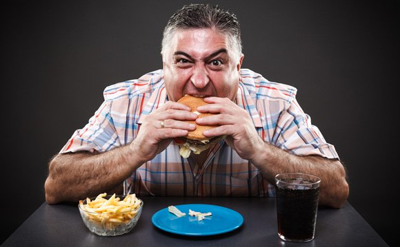 greedy overweight man eating junk food